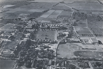 Photo: Aerial photograph of Davis campus, looking west, taken in 1938; from the air, one may see North, South, East and West Hall, Walker and Hart Hall, Hickey Gym and Toomey Field, while in the distance the fields that are later developed into Segundo Area, Tercero Area, and campus apartments may be seen.